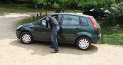 man reconstructing breaking into a vehicle