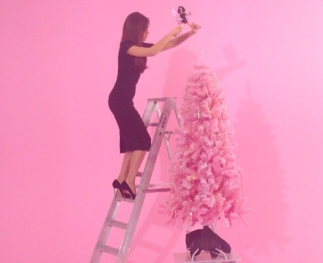 Victoria Beckham decorating a christmas tree in high heels