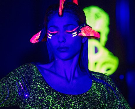 A model wears neon face paint and a neon wig at Paris Fashion Week.