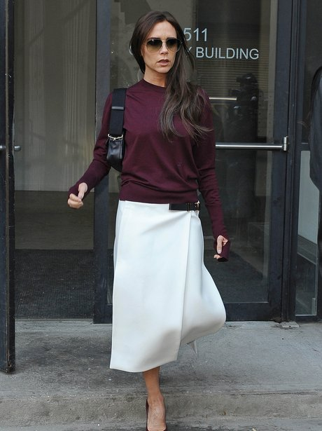 Victoria Beckham in purple jumper and white skirt