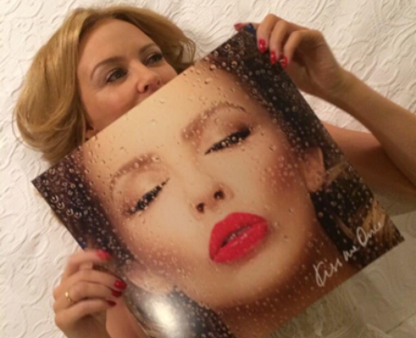 Kylie lying on a bed with her album artwork