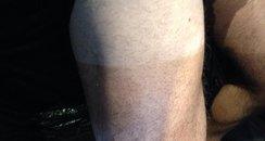 Tom's tanned leg