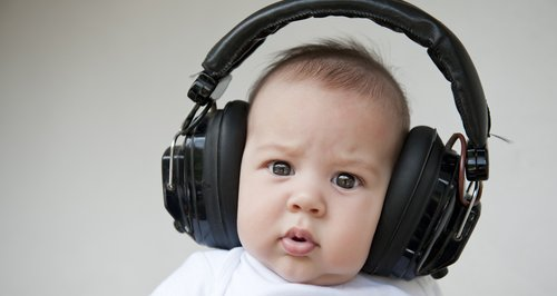 confused baby with headphones in